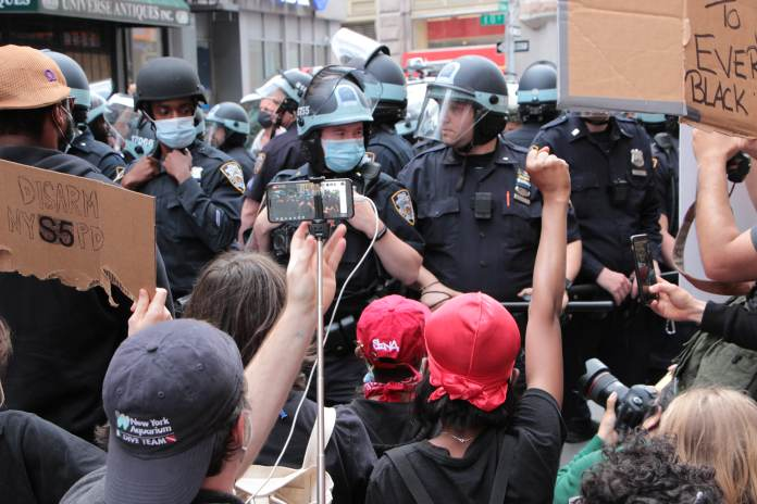 Protesters kneel in front of police during a demonstration on Broadway near New York City's Union Square, June 2, 2020.
