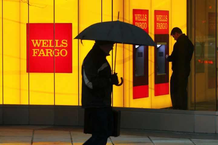A man walks past a Wells Fargo Bank branch on a rainy morning in Washington.