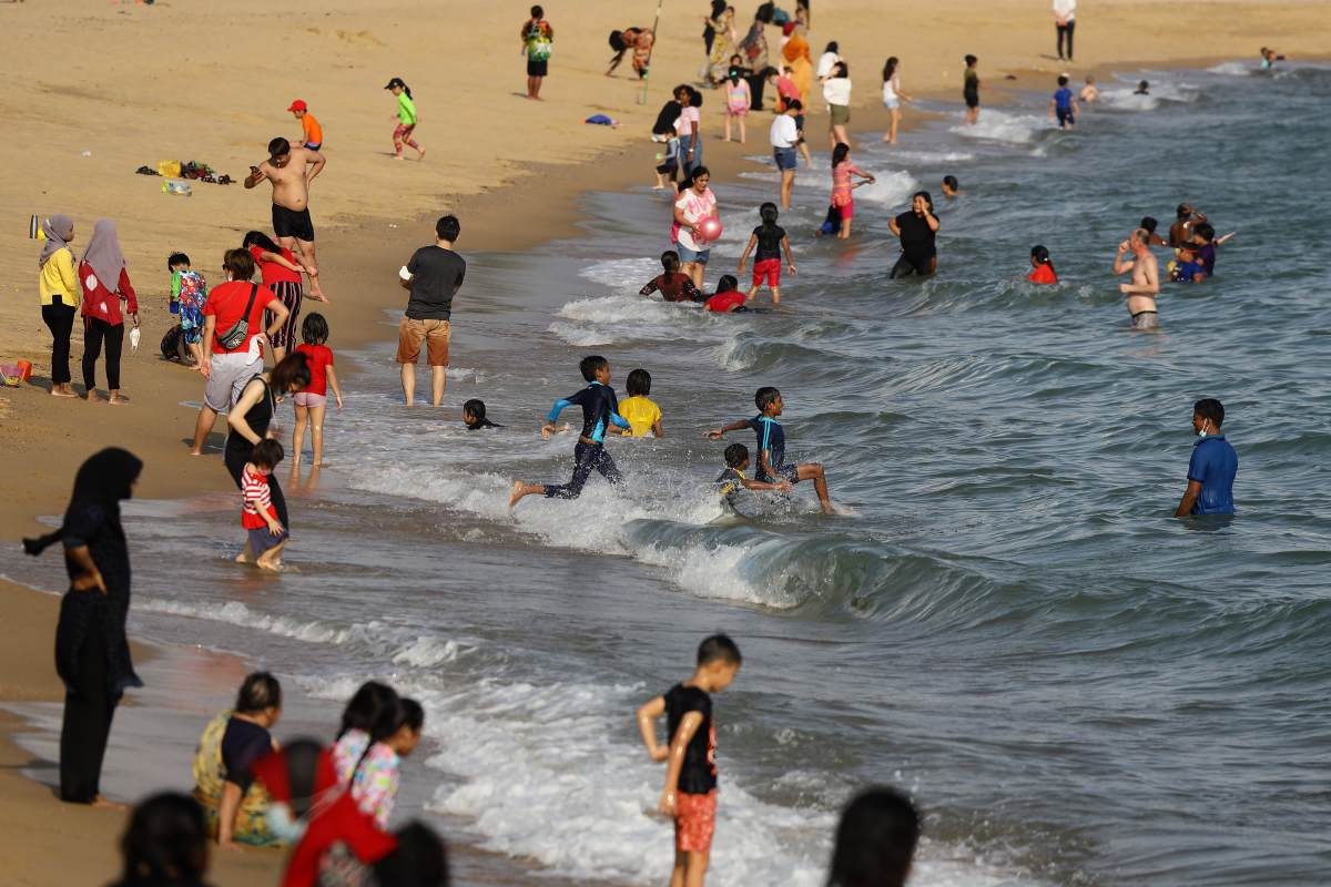 People swim at a beach at East Coast Park on December 25, 2020 in Singapore.