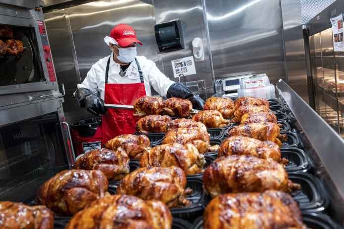 A worker wearing a protective mask removes rotisserie chicken from skewers inside a Costco store in San Francisco, California, on Wednesday, March 3, 2021.