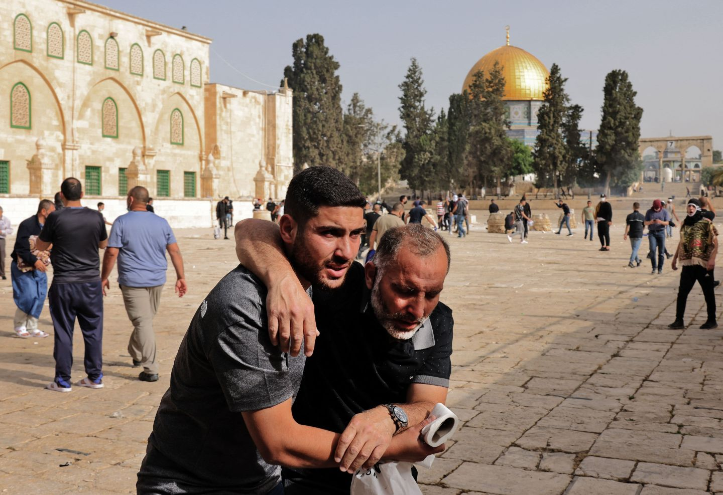 A Palestinianman helps a wounded fellow protester amid clashes with Israeli security forces at Jerusalem's Al-Aqsa mosque compound on May 10, 2021, ahead of a planned march to commemorate Israel's takeover of Jerusalem in the 1967 Six-Day War.