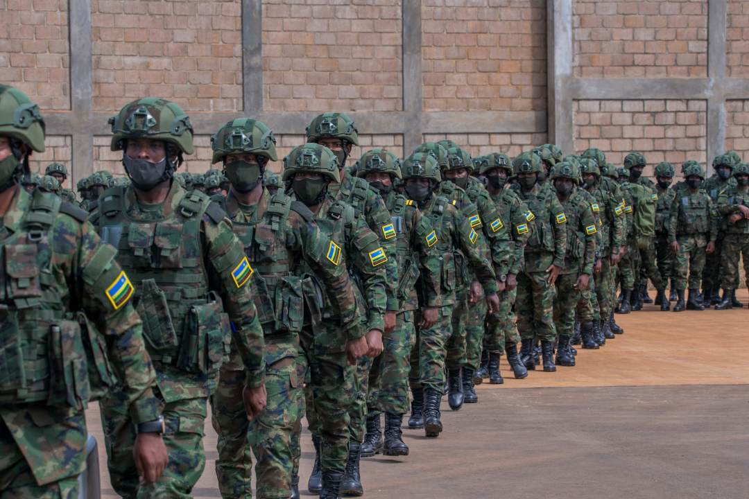 KIGALI, Rwanda - Rwandan soldiers wait to board a plane for Mozambique in Kigali, capital city of Rwanda, July 10, 2021. The Rwandan government on Friday started deploying a 1000-member joint force of army and police personnel to Mozambique to support efforts to restore state authority in the latter's restive region.
