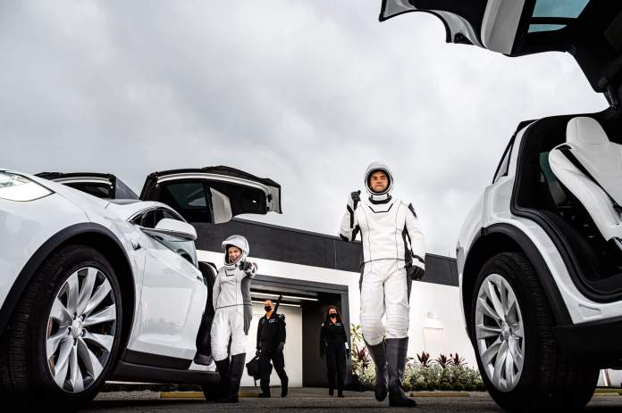 Hayley Arceneaux, left, and Jared Isaacman walk out and board the Tesla Model Xs that will take them to the launchpad during a launch rehearsal on September 12, 2021.