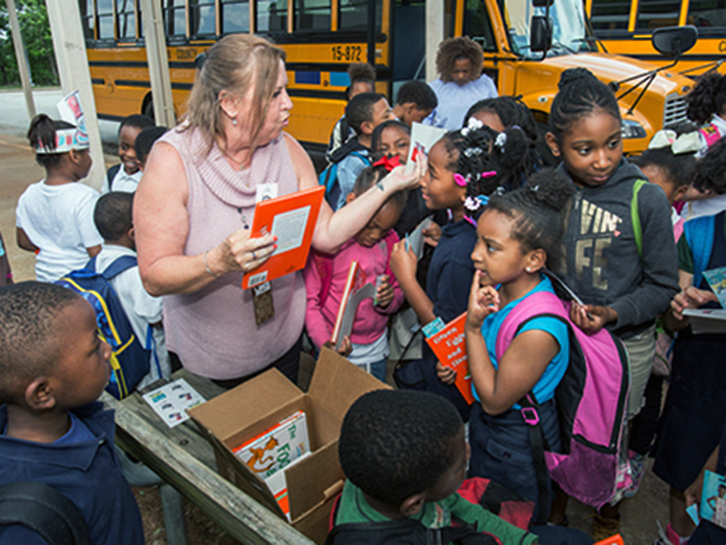 bus driver Deborah Lazarus hands out books to students