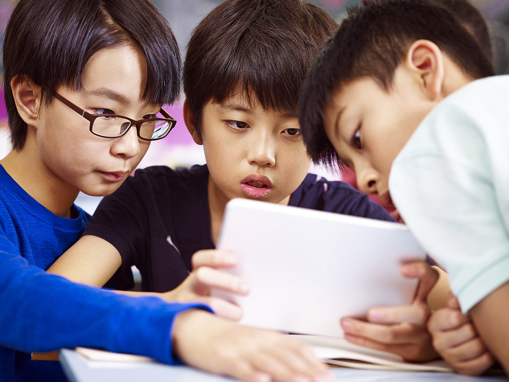 Students in Singapore work on a tablet
