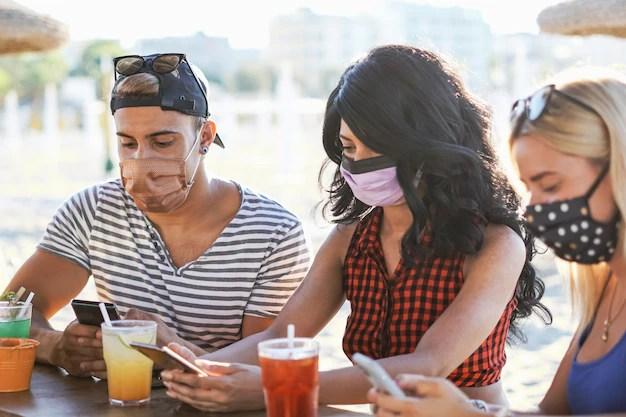 Amigos usando el teléfono inteligente en el bar de la playa con mascarilla    Foto Premium