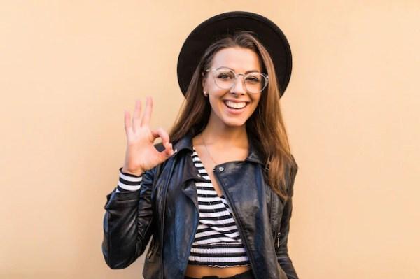 Chica de moda hermosa en chaqueta de cuero y sombrero negro muestra signo ok aislado en la pared de color amarillo claro Foto gratis