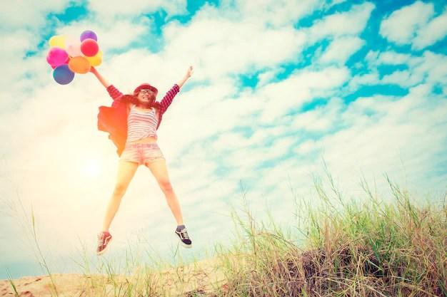 Chica saltando en la playa con globos de colores Foto gratis
