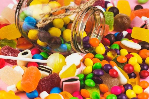 Derramó caramelos de colores de tarro de cristal Foto gratis