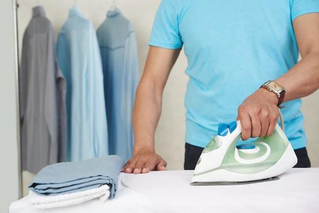 Hombre irreconocible planchado de camisas y lavandería en casa Foto gratis