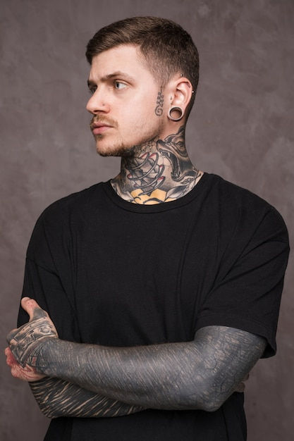 Hombre Joven Tatuado Con Piercing En Sus Orejas Y Nariz Con El Brazo