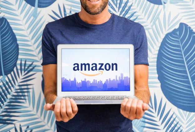 Hombre sosteniendo portátil con sitio de amazon Foto gratis