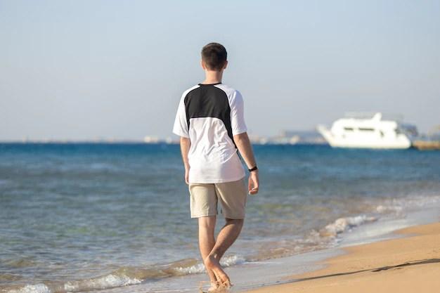 Joven caminando en la costa Foto gratis