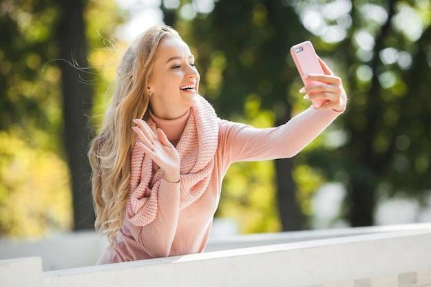 Mujer joven hablando por teléfono celular. linda dama haciendo selfie Foto Premium