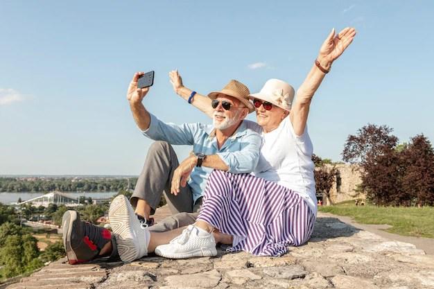 Mujer levantando las manos mientras toma una selfie Foto gratis