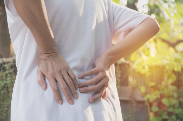 Una mujer que sufre de dolor de espalda lesión espinal y ...