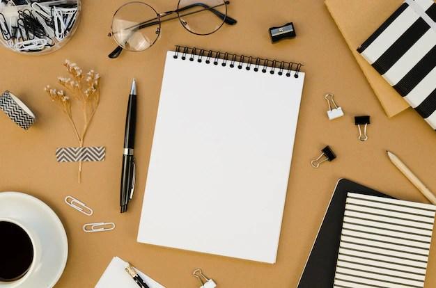 Plano de escritorio con libreta y gafas Foto gratis