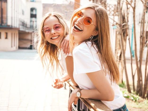 Retrato de dos jóvenes hermosas rubias sonrientes chicas hipster en ropa de moda verano camiseta blanca. . modelos positivos divirtiéndose en gafas de sol. Foto gratis