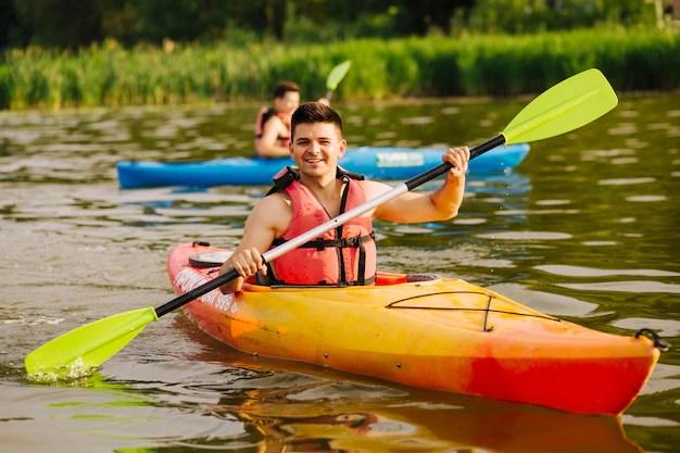 Sonriente hombre remando un kayak en el lago Foto gratis