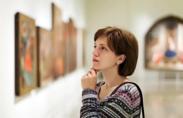 Visitante buscando fotos en la galería de arte Foto gratis