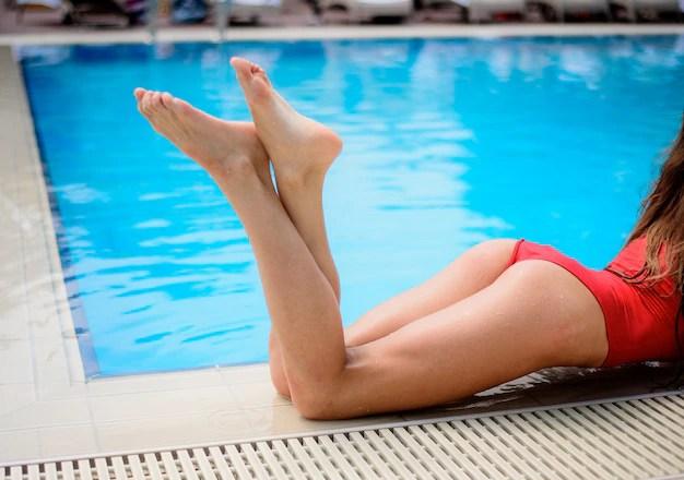 Ragazza in costume da bagno rosso in piscina blu