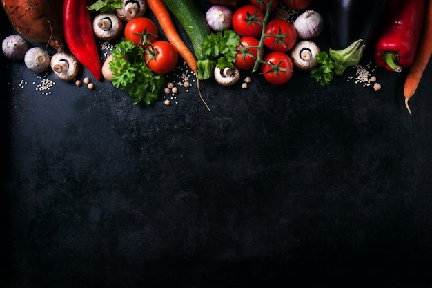 Varie verdure su un tavolo nero con spazio per un messaggio  Scaricare foto gratis