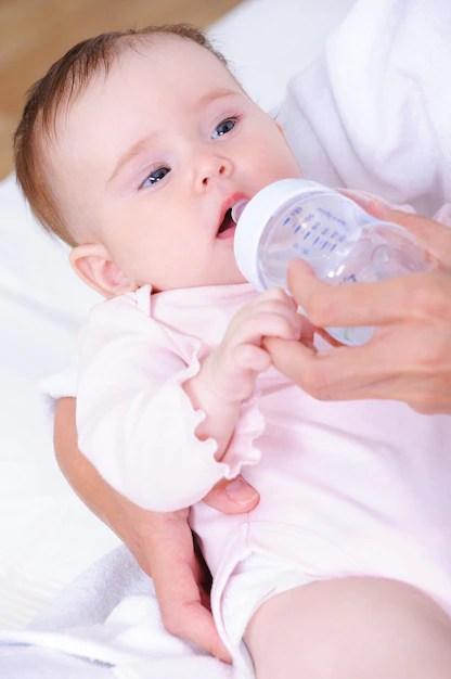 Bebê com mamadeira de plástico no colo