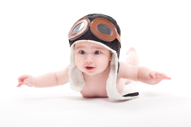 Bebê com chapéu de piloto deitado de barriga para baixo em fundo branco