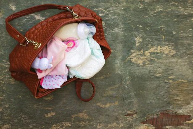 Bolsa de maternidade aberta com roupinhas de bebê, mamadeira e fraldas