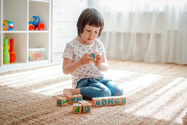 Brincadeiras com blocos de madeira com letras no jardim de infância da casa da torre da sala do assoalho. Foto Premium