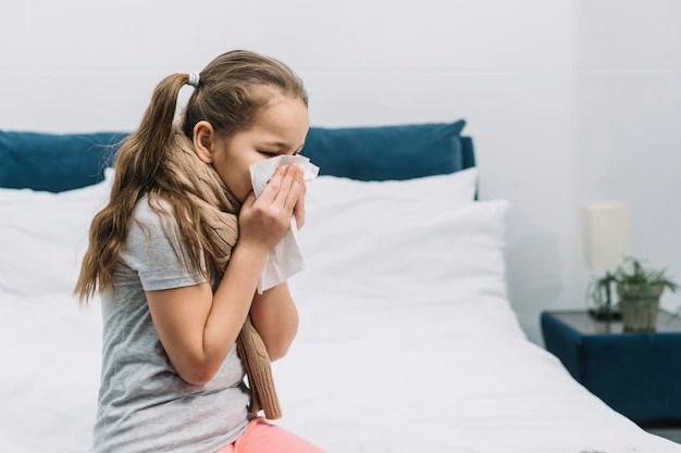 Menina sentada na cama tossindo em lenço