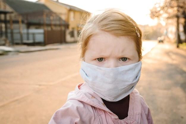 Criança com máscara na rua