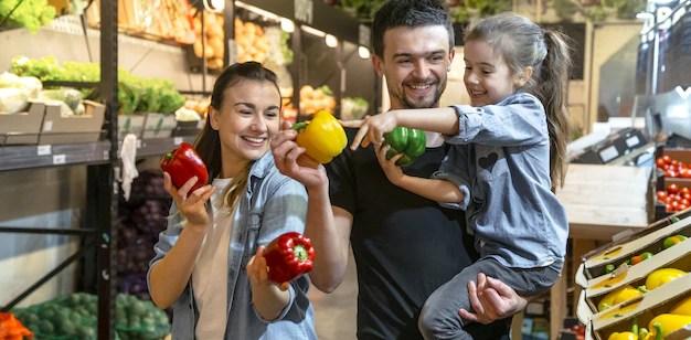 Família feliz compra legumes. família alegre de três escolhendo tomates no departamento de vegetais de supermercado ou mercado. sobrepeso
