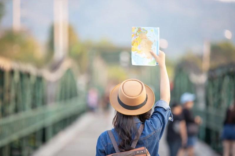 na imagem uma mulher está de costas, com o braço levantado segurando um mapa nas mãos, o fundo da imagem está borrado e a imagem focada nela. | Como organizar uma viagem para qualquer lugar no mundo