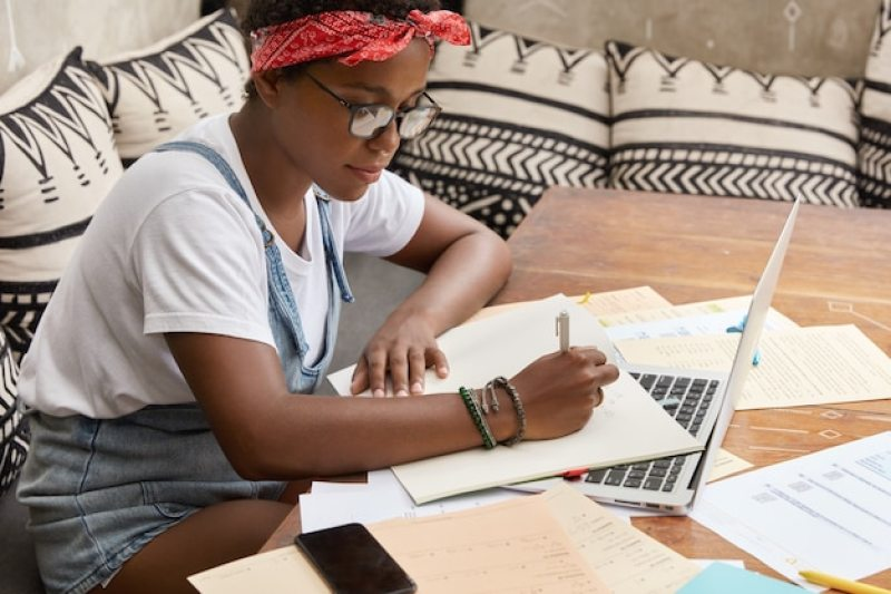na imagem uma estudante ocupada estudando utilizando papéis e o computador | O guia do servidor público de como se organizar financeiramente