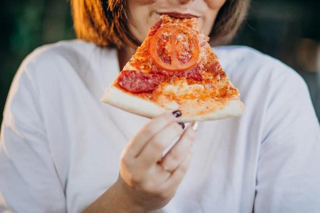 Mulher com fome comendo pizza apetite