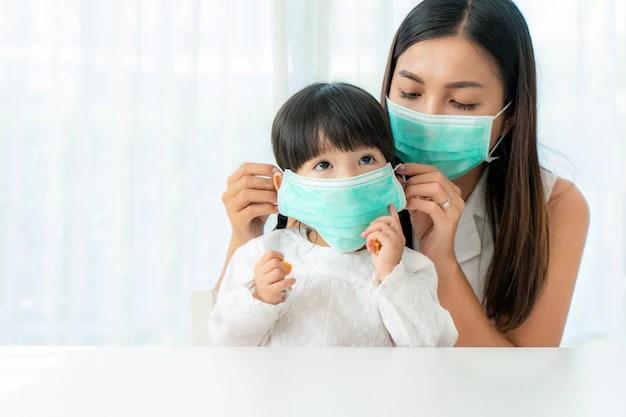 Mãe colocando máscara de proteção em criança pequena devido ao coronavírus