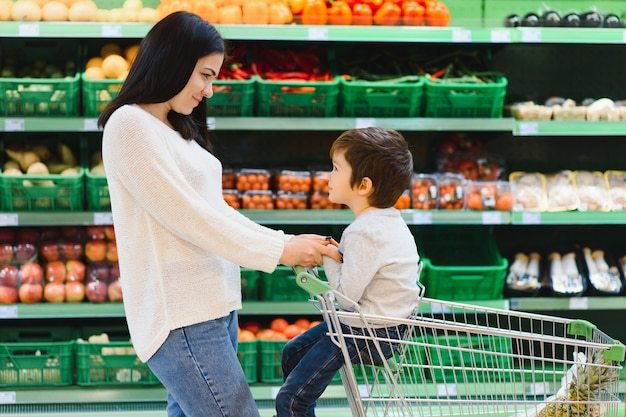 Mãe e filho no mercado conversando em corredor de frutas e vegetais