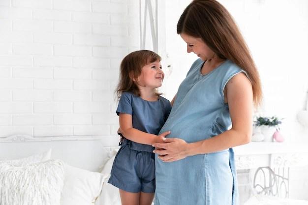 Gestante abraçando filha