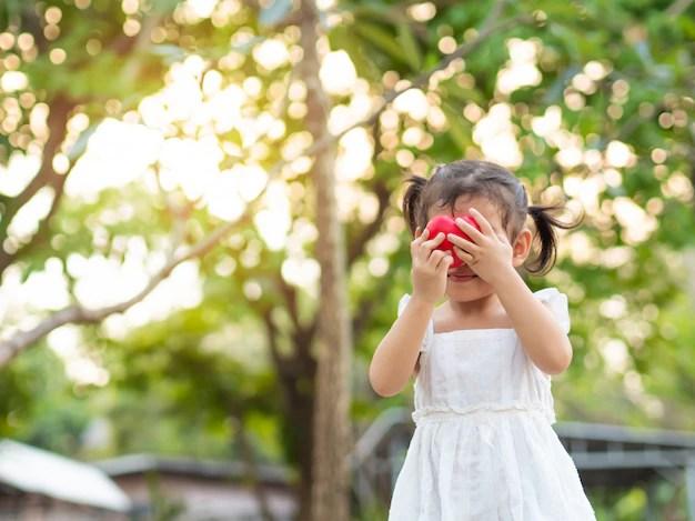 Menina bonita segurando um coração vermelho ansiedade infantil