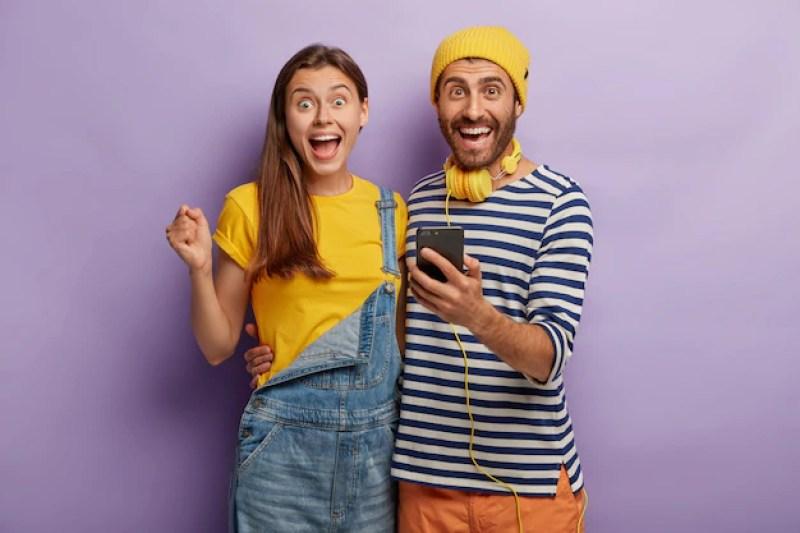 na imagem dois jovens uma menina e menino estão felizes e se abraçam, se divertem, seguram o telefone celular, estão empolgados com a ideia de um futuro financeiramente tranquilo |Como planejar e como funciona a aposentadoria?