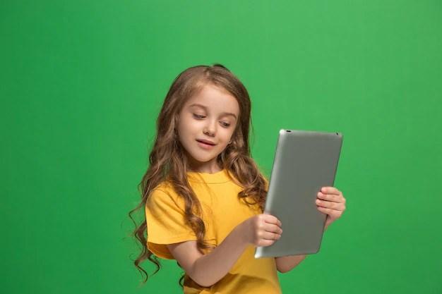 Menina com tablet em fundo verde