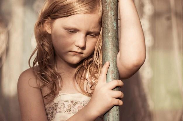Menina triste encostada em poste