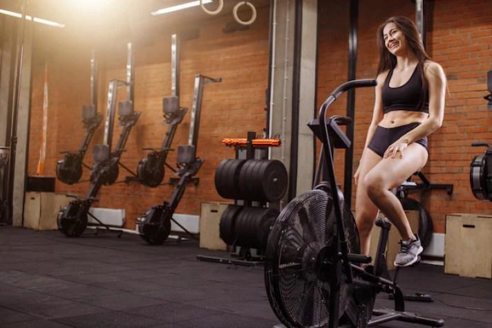 Mulher andando de bicicleta ergométrica no ginásio. garota apta a fazer cardio-treinamento em bicicleta   Foto Premium