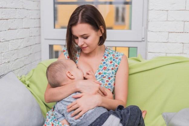 Mulher feliz que amamenta seu filho amamentar