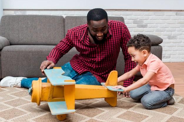 Pai e filho brincando com avião de madeira em quarentena coronavírus
