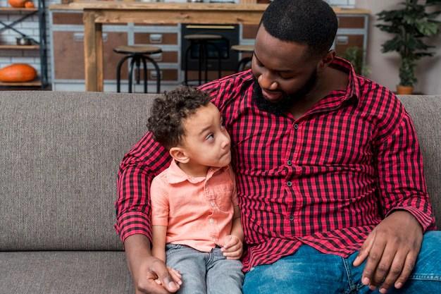 Pai e filho conversando no sofá de casa sobre quarentena coronavírus