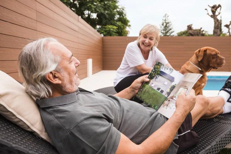 na imagem um homem e uma mulher idosos aproveitam seu tempo após a aposentadoria juntos com um cachorro em um jardim com piscina | Como planejar e como funciona a aposentadoria?
