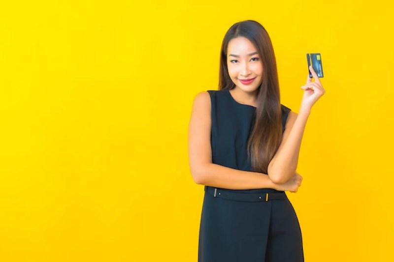 na imagem  uma mulher de negócios jovem com cartão de crédito em fundo amarelo  | O Guia do Cartão de Crédito