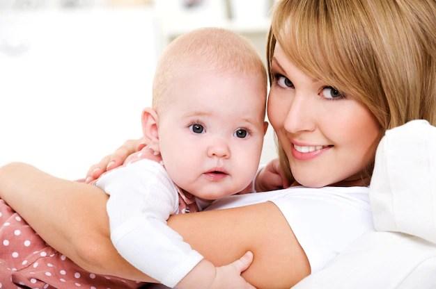 Mãe e bebê, abraçados olhando para câmera